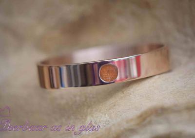 Armband RVS in de kleur rosé met crematie as en brons kleur glas, het toplaagje is belegd met hars.Sieraad wordt in eigen atelier bewerkt door Jet. Prijs inclusief crematie as verwerking 79,95 euro.