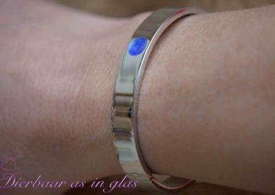 Armband RVS in de kleur zilver met crematie as en blauw kleur glas, het toplaagje is belegd met hars.Sieraad wordt in eigen atelier bewerkt door Jet. Prijs inclusief crematie as verwerking 79,95 euro.