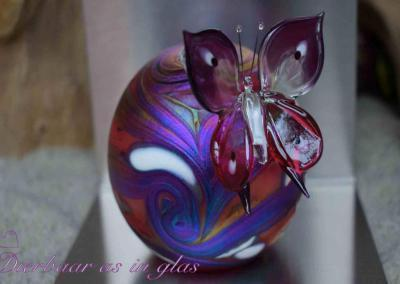 Crematie as handgemaakte urn van glas Elan collectie, red bulb, inhoud 100ml, afmeting 8cm,Verkoopprijs 129,00 euro. Meerdere kleuren en maten mogelijk! De urn is gepersonaliseerd met een bijpassende vlinder, afmeting 5 cm. Verkoopprijs vlinder 26,95 euro.Dierbaar as in glas is gespecialiseerd in het personaliseren van urnen en dealer van alle producten van de Eeuwige Roos