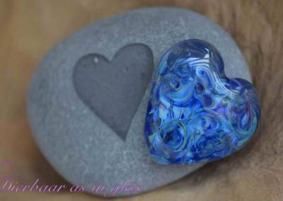 Gedenksteen waar crematie as hart van glas op gemonteerd is. De stenen variëren van 7 t/m 10 cm. Getoonde foto laat een set zien met een groot hart van zilverglas. Prijs zoals getoond, inclusief verwerking crematie as in glas is 104,95 euro