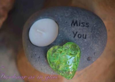 Gedenksteen theelicht waar crematie as hart van glas op gemonteerd is. De gedenkstenen met theelicht variëren van 12 t/m 17 cm. Getoonde foto laat een set zien met een groot hart van glas. Prijs zoals getoond, inclusief verwerking crematie as in glas is 124,95 euro