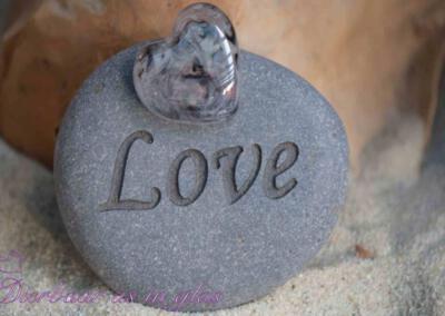 Gedenksteen waar crematie as hart van glas op gemonteerd is. De stenen variëren van 7 t/m 10 cm. Getoonde foto laat een set zien met een middel groot hart van glas. Prijs zoals getoond, inclusief verwerking crematie as in glas is 106,95 euro