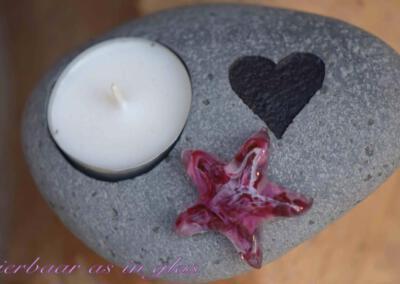 Gedenksteen theelicht waar crematie as ster van glas op gemonteerd is. De gedenkstenen met theelicht variëren van 12 t/m 17 cm. Getoonde foto laat een set zien met een middel grote ster van glas. Prijs zoals getoond, inclusief verwerking crematie as in glas is 114,95 euro