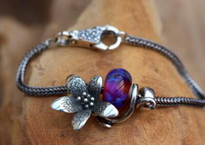 Armband belegd met een 925 zilveren lotus bloem waarin een crematie-as glas bedel verwerkt is. De bloem wordt tussen 2 rvs stoppers tegen gehouden tegen schuiven.Prijs gehele set 124,95 euro