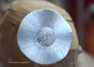 Crematie as in glas sieraad,Prijs 129,95 euro. Zie voor meer details over het sieraad op bol.com via Urnen met naam en symbool