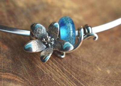 bloemsieraad  van 925 zilver met transparant blauwe crematie as glasbedel aan spang