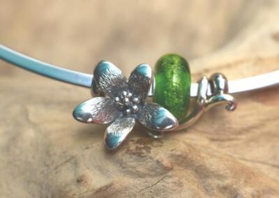 bloemsieraad  van 925 zilver met transparant groene crematie as glasbedel aan spang