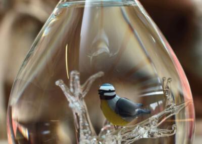Urn waarbij het crematie-as vast in de urn is geblazen. Persoonlijke wensen zijn ook bespreekbaar, Urn Pimpelmeesje op met crematie as in de takjes geblazen. Prijs 275 euro