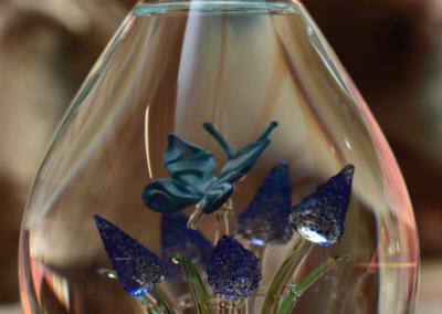 Urn waarbij het crematie-as vast in de urn is geblazen. Persoonlijke wensen zijn ook bespreekbaar, Urn vlinder op blauwe druifjes waarin het crematie-as is geblazen.Prijs 275 euro.Deze urnen zijn niet online verkrijgbaar, maar u bent van harte welkom in onze showroom om een indruk te krijgen van deze unieke glaskunst!